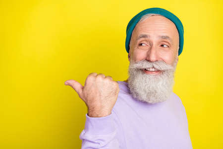 Photo portrait of senior curious dreamy man pointing thumb copyspace advising choosing isolated bright yellow color background