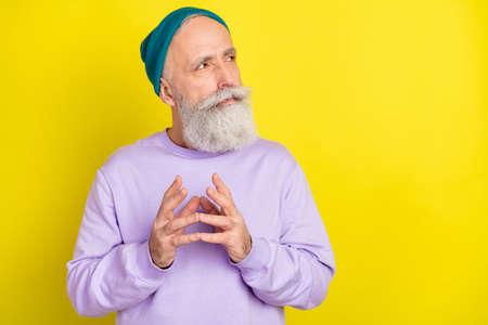 Photo portrait of serious smart aged man got idea looking empty space isolated vivid yellow color background