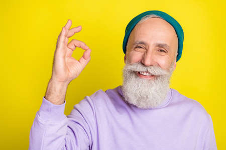 Photo portrait of aged man showing okay sign with fingers smiling isolated bright yellow color background Stok Fotoğraf