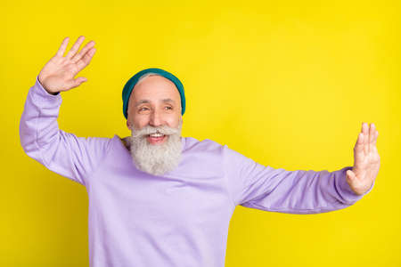 Photo portrait of aged man smiling dancing on holidays looking empty space isolated vivid yellow color background