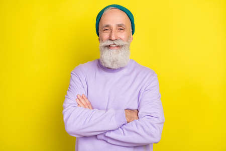 Photo portrait of aged man smiling happy with folded hands isolated vibrant yellow color background Stok Fotoğraf