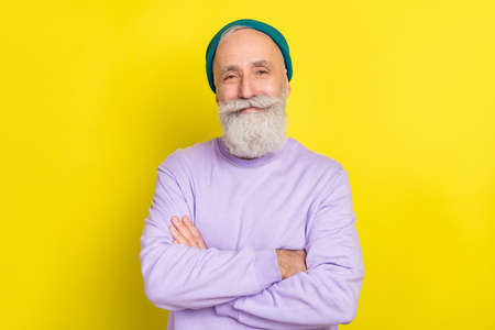 Photo portrait of aged man smiling cheerful nice with folded hands isolated vibrant yellow color background