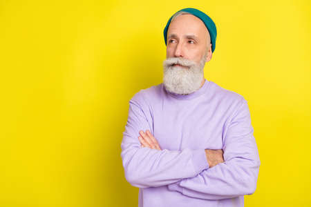 Photo portrait of aged man serious smart looking copyspace with crossed hands isolated vibrant yellow color background