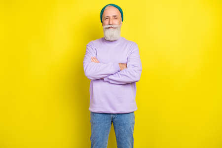 Photo portrait of aged man smiling happy with crossed hands in casual clothes isolated vibrant yellow color background