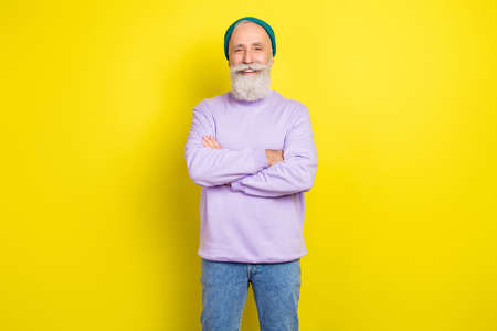 Photo portrait of aged man smiling cheerful with folded hands in stylish clothes isolated vibrant yellow color background