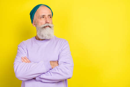 Photo portrait of aged man serious confident looking copyspace with crossed hands isolated vibrant yellow color background