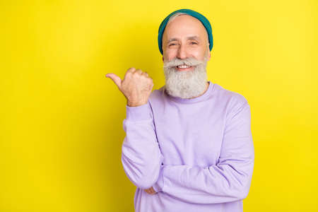 Photo portrait of aged man smiling showing empty space with thumb isolated bright yellow color background Stok Fotoğraf