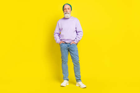 Full length body size photo of serious confident man wearing stylish clothes isolated on bright yellow color background