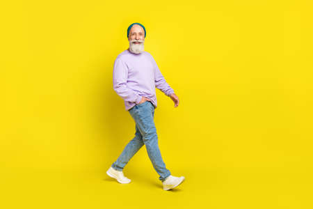 Full length body size photo of smiling elder man wearing stylish clothes going forward isolated on bright yellow color background