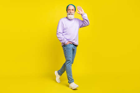 Full length body size photo of smiling elder man going forward waving hand greeting isolated on bright yellow color background