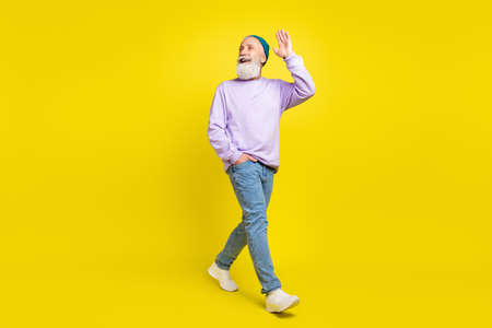 Photo of friendly cute age gentleman wear violet sweater headwear walking smiling waving arm isolated yellow color background Stok Fotoğraf