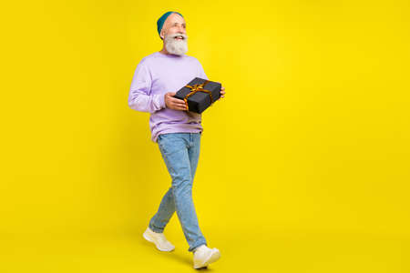 Photo of sweet excited mature man dressed purple pullover smiling walking holding gift box empty space isolated yellow color background