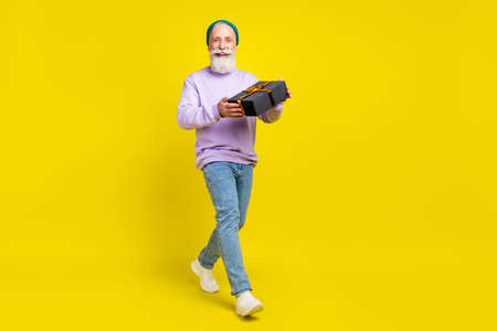 Photo of cute attractive age gentleman wear violet sweater walking smiling holding present isolated yellow color background