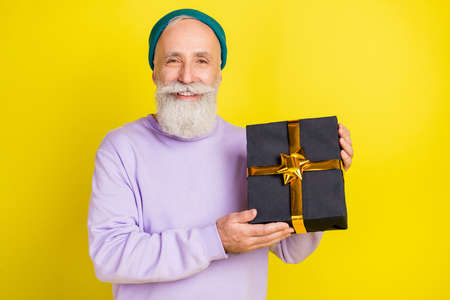 Photo of excited handsome mature man dressed purple pullover headwear holding gift box isolated yellow color background