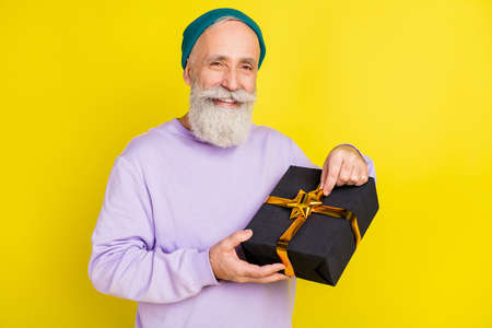 Photo of attractive sweet age gentleman wear violet sweater headwear smiling opening present isolated yellow color background Stok Fotoğraf