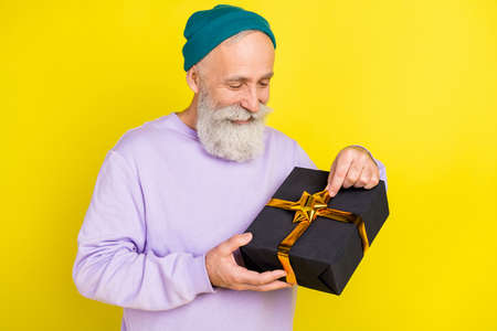 Photo of handsome cute mature man dressed purple pullover headwear smiling opening gift box isolated yellow color background