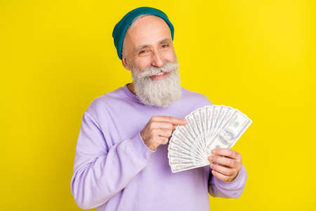 Photo of cute pretty mature man dressed purple pullover headwear smiling counting money isolated yellow color background