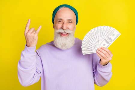 Photo of funky sweet age gentleman wear violet sweater showing hard rock sign holding money isolated yellow color background