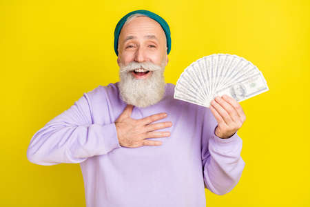 Photo of pretty impressed mature man dressed purple pullover headwear holding money arm chest isolated yellow color background Stok Fotoğraf