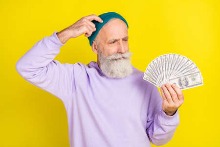 Photo of sweet thoughtful age gentleman wear violet sweater headwear arm head holding money isolated yellow color background