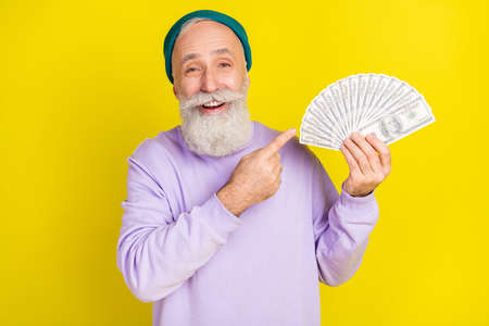 Photo of impressed pretty mature man dressed purple pullover smiling pointing finger money fan isolated yellow color background