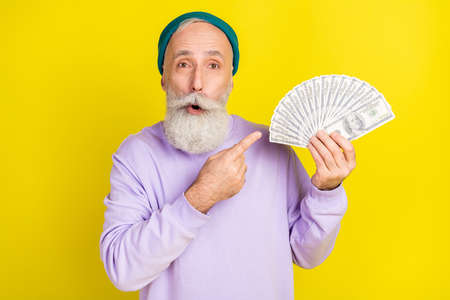 Photo of shocked funny age gentleman wear violet sweater headwear pointing money big eyes isolated yellow color background Stok Fotoğraf
