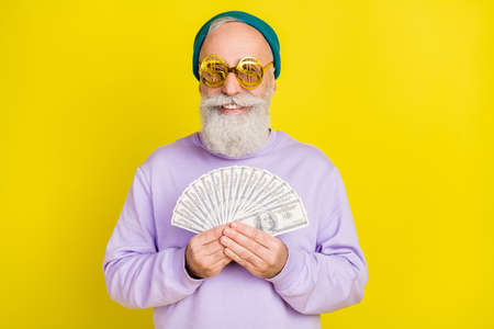 Photo of pretty funky mature man dressed purple pullover eyewear smiling holding money fan isolated yellow color background