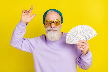 Photo of funny cute age gentleman wear violet sweater headwear eyeglasses holding money dancing isolated yellow color background