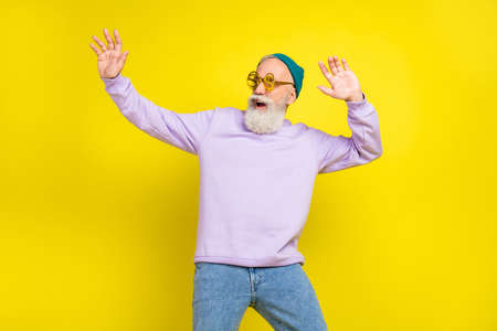 Photo of funky sweet mature man dressed purple pullover headwear eyewear smiling dancing isolated yellow color background Stok Fotoğraf