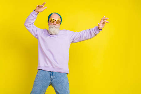 Photo of cute cool age gentleman wear violet sweater headwear eyeglasses dancing isolated yellow color background Stok Fotoğraf