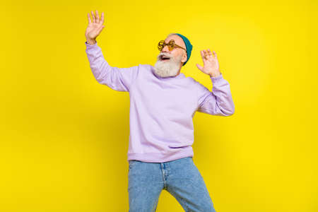 Photo of sweet attractive mature man dressed purple pullover headwear eyewear smiling dancing isolated yellow color background