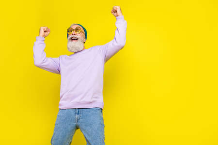 Photo of cool lucky age gentleman wear violet sweater eyeglasses rising fists looking empty space isolated yellow color background