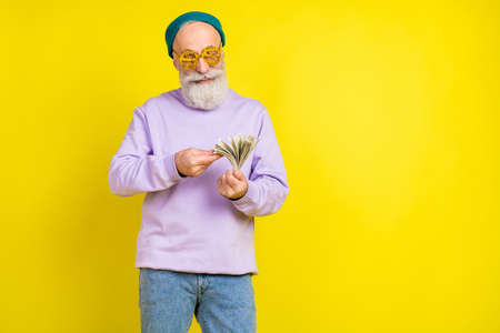 Photo of attractive pretty mature man dressed purple pullover eyewear counting money empty space isolated yellow color background
