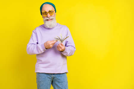 Photo of lucky funny age gentleman wear violet sweater headwear eyeglasses counting dollars empty space isolated yellow color background