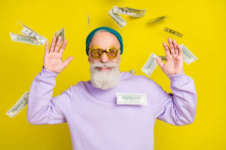 Photo of pretty funky mature man dressed purple pullover headwear eyewear flying money isolated yellow color background