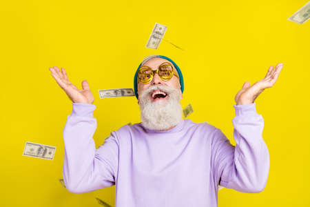 Photo of funny charming age gentleman wear violet sweater headwear eyeglasses catching flying dollars isolated yellow color background