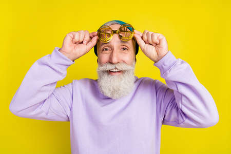 Photo of funky positive mature man dressed purple pullover headwear arms eyewear smiling isolated yellow color background