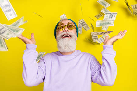 Photo of charming cheerful age gentleman wear violet sweater eyeglasses catching flying dollars isolated yellow color background
