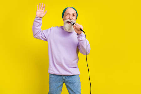 Photo of positive attractive mature man dressed purple pullover singing karaoke rising arm isolated yellow color background