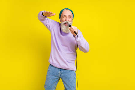 Photo of cheerful funny age gentleman wear violet sweater headwear dancing singing isolated yellow color background Stok Fotoğraf