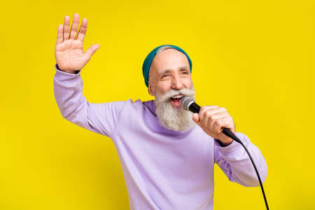 Photo of attractive sweet mature man dressed purple pullover headwear singing karaoke rising palm isolated yellow color background