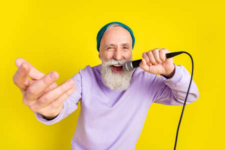 Photo of funny positive age gentleman wear violet sweater headwear dancing singing isolated yellow color background