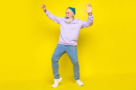 Photo of sweet handsome mature man dressed purple pullover headwear dancing smiling isolated yellow color background