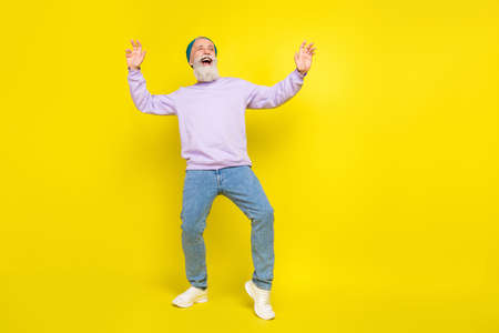 Photo of positive funky age gentleman wear violet sweater headwear smiling dancing isolated yellow color background Stok Fotoğraf