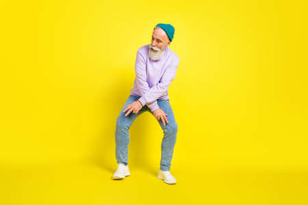Photo of handsome attractive mature man dressed purple pullover headwear dancing smiling isolated yellow color background