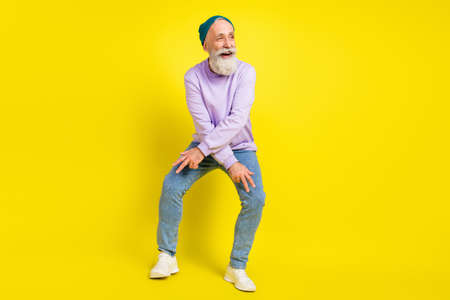 Photo of funky cheerful age gentleman wear violet sweater headwear smiling dancing isolated yellow color background