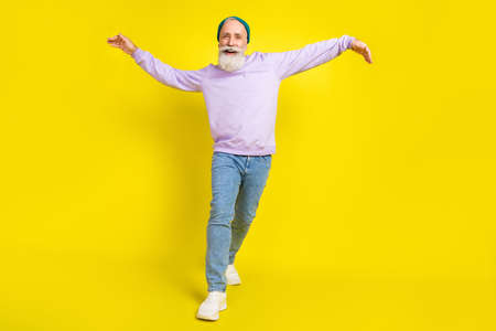 Photo of attractive positive mature man dressed purple pullover headwear dancing smiling isolated yellow color background Stok Fotoğraf