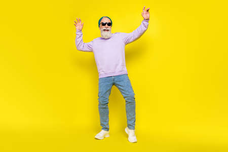 Photo of cheerful cute age gentleman wear violet sweater headwear dark glasses smiling dancing isolated yellow color background Stok Fotoğraf