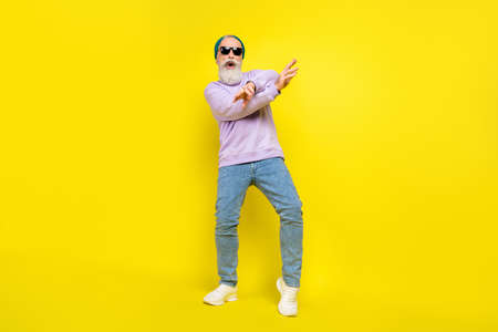 Photo of positive pretty mature man dressed purple pullover headwear dark spectacles dancing isolated yellow color background