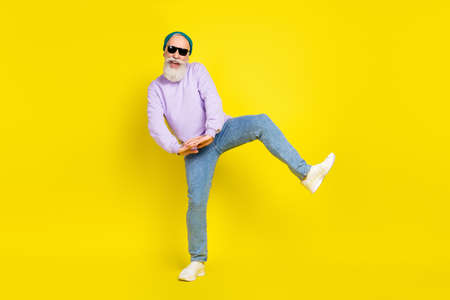 Photo of cute sweet age gentleman wear violet sweater headwear dark glasses smiling dancing isolated yellow color background Stok Fotoğraf